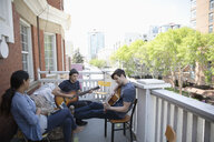Millennial friends hanging out, playing guitars on apartment balcony - HEROF11824