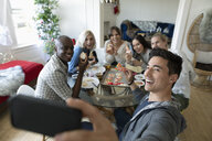Millennial friends with camera phone taking selfie, posing with decorated Christmas sugar cookies - HEROF11854