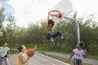 Playful teenage girls playing basketball at park basketball court - HEROF11878