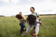 Playful teenage girl friends piggybacking in rural field - HEROF11884