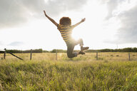 Playful teenage girl jumping for joy in sunny rural field - HEROF11887