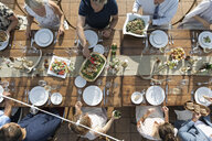 Overhead view friends enjoying lunch and wine at patio table - HEROF11890