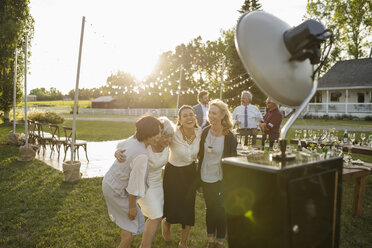 Playful women friends posing at photo booth at wedding party in sunny rural garden - HEROF11893