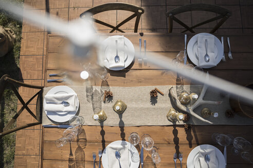 Overhead view placesettings on sunny patio table - HEROF11905