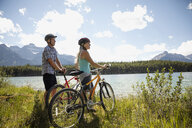 Mature couple mountain biking along sunny remote lake, Alberta, Canada - HEROF11938