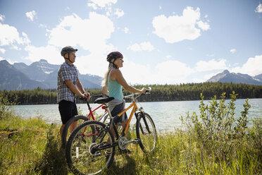 Mature couple mountain biking along sunny remote lake, Alberta, Canada - HEROF11938