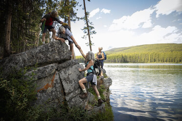 Mature couples hiking, scaling rock at forest lakeside, Alberta, Canada - HEROF11953