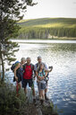 Mature couples hiking, taking selfie with camera phone at forest lakeside, Alberta, Canada - HEROF11956