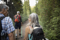 Mature couple hiking on forest trail - HEROF11962
