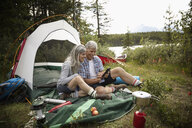 Mature couple relaxing, using digital tablet by tent at forest campsite, Alberta, Canada - HEROF11965