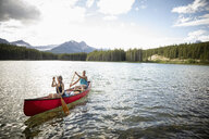 Mature couple canoeing on sunny tranquil lake, Alberta, Canada - HEROF11971