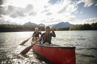 Mature women canoeing on sunny, tranquil lake, Alberta, Canada - HEROF11974