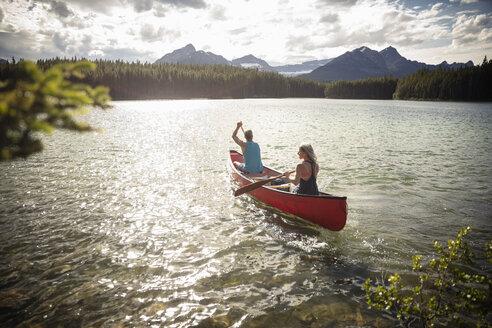 Mature couple canoeing on sunny, tranquil lake, Alberta, Canada - HEROF11977