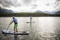 Mature men enjoying standing paddleboarding on lake, Alberta, Canada - HEROF11980