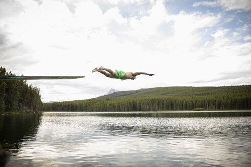 Mature man diving off diving board into lake, Alberta, Canada - HEROF11989