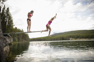 Mature women jumping off diving board into lake, Alberta, Canada - HEROF11992