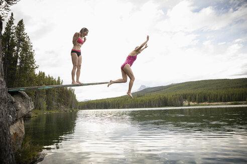 Mature women jumping off diving board into lake, Alberta, Canada - HEROF11992