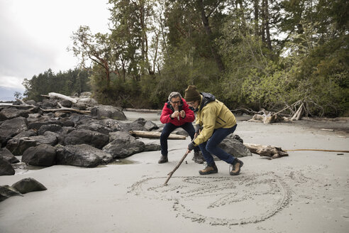 Affectionate active senior couple drawing heart-shape in wet sand on rugged beach - HEROF12007