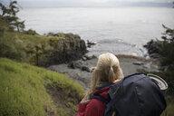 Active senior woman backpacking on cliff overlooking ocean - HEROF12013