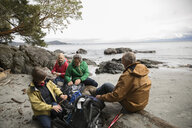 Active senior couple friends backpacking, resting on rugged beach - HEROF12019