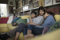 Affectionate mother and tween daughter and son cuddling on sofa - HEROF12037