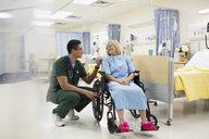 Male nurse talking to woman in hospital wheelchair - HEROF12085