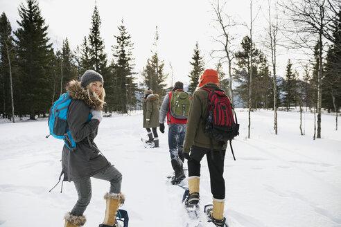 Friends snowshoeing in snowy field - HEROF12184