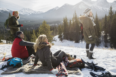 Friends relaxing on blanket with snowy mountain view - HEROF12190