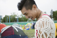 Laughing young man looking down at summer music festival campsite - HEROF12268