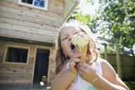 Girl eating melting messy ice cream cone in sunny backyard - HEROF12301