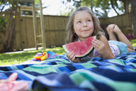 Girl laying on blanket eating watermelon in backyard - HEROF12304