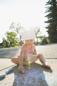 Girl drawing with sidewalk chalk on sunny sidewalk - HEROF12322