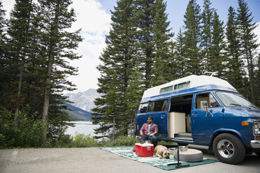 Man and dog relaxing outside camper van at remote lakeside - HEROF12337