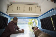 Man and dog sitting at table in the back of camper van at lakeside - HEROF12340