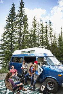 Friends hanging out talking outside camper van in woods - HEROF12343
