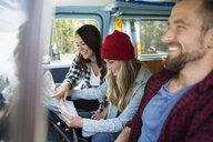 Laughing friends viewing map in camper van - HEROF12346