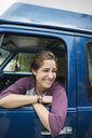 Laughing woman leaning out window of camper van - HEROF12349