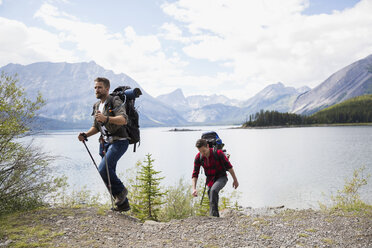 Male friends hiking with backpacks and hiking poles at remote mountain lakeside - HEROF12355