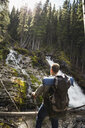 Man hiking with backpack enjoying waterfall view in woods - HEROF12364