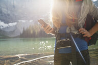 Female hiker with camera using cell phone at sunny lakeside - HEROF12373
