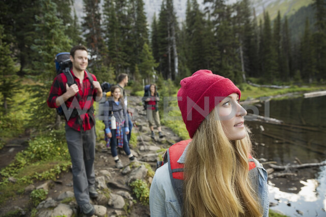 Friends hiking along lake on trail in remote woods - HEROF12379