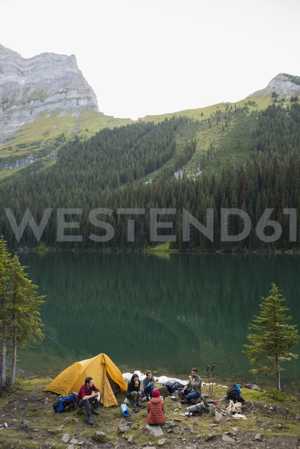 Friends camping at remote lakeside campsite - HEROF12382