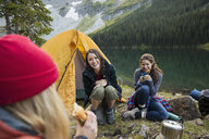 Female friends camping at remote lakeside campsite - HEROF12385
