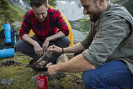 Male friends cooking bacon in skillet over kerosene camping stove at campsite - HEROF12388