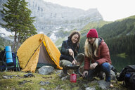 Female friends cooking with skillet over kerosene camping stove at remote campsite - HEROF12391