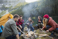 Friends laughing and hanging out around campfire at remote lakeside - HEROF12400