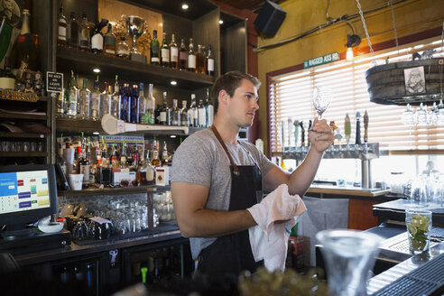 Male bartender drying glass behind counter - HEROF12421