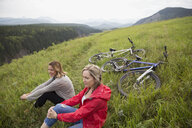 Female friends relaxing near mountain bikes in grass in remote rural field - HEROF12436