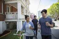 Young couple with coffee walking bicycle on neighborhood sidewalk - HEROF12451