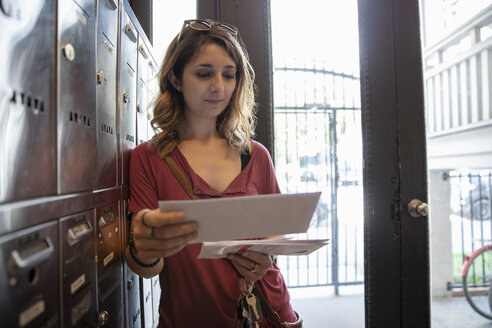 Young woman checking mailbox in apartment entrance - HEROF12457